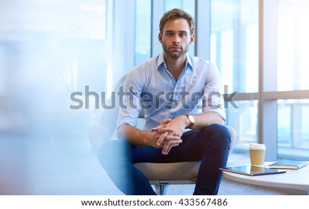 Portrait of a handsome young entrepreneur sitting in a modern business meeting space, and looking intently at the camera - stock photo