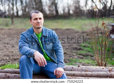 Portrait of a handsome young farmer sitting on a pile of logs, with ploughed land in background - stock photo