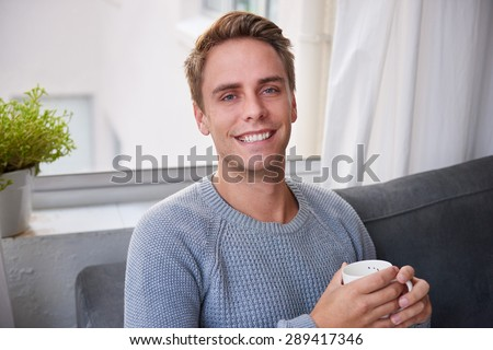 Portrait of a handsome young guy holding a cup of coffee and sitting on his couch at home while smiling confidently - stock photo