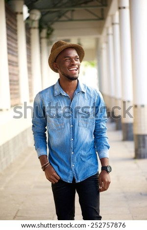 Portrait of a handsome young happy man walking outside with hat