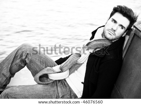 Portrait of a handsome young lying on wooden texture. - stock photo