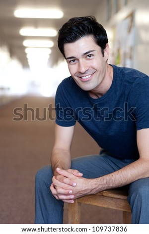 portrait of a handsome young male student inside a school - stock photo