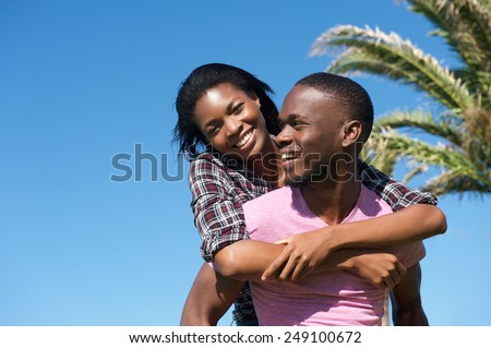 Portrait of a handsome young man carrying attractive woman on his back outdoors - stock photo