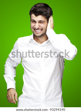 portrait of a handsome young man covering his ears over a green background
