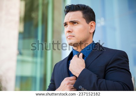Portrait of a handsome young man in a suit getting ready for an interview and fixing his tie - stock photo