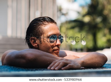 Portrait of a handsome young man in a swimming pool looking aside