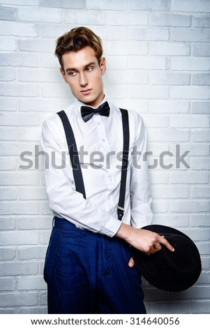 Portrait of a handsome young man in elegant suit posing by a white brick wall. Business.