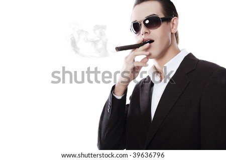 Portrait of a handsome young man in elegant suit smoking a cigar. - stock photo