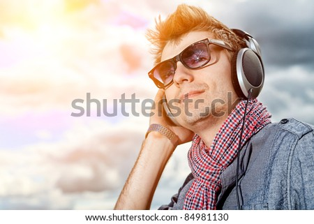 Portrait of a handsome young man in headphones posing outdoor.