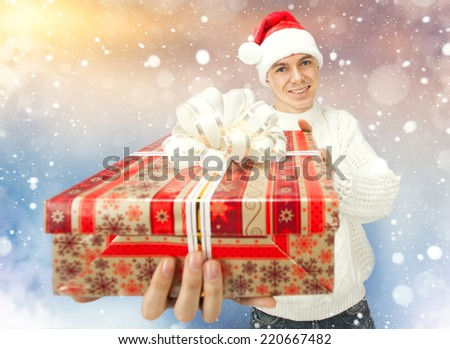 Portrait of a handsome young man in Santa Claus hat holding big red gift box - stock photo
