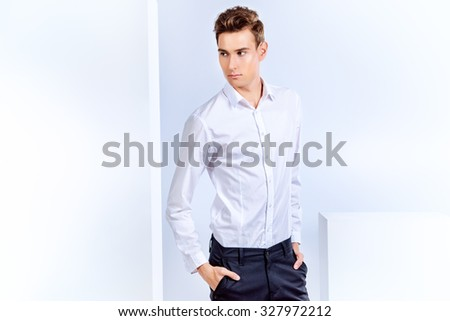 Portrait of a handsome young man in white shirt. Men's beauty, fashion. Studio shot. Isolated over white background.
