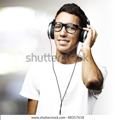 portrait of a handsome young man listening to music indoor - stock photo