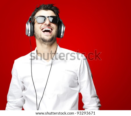 portrait of a handsome young man listening to music with headphones over a red background