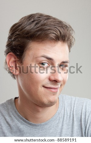 portrait of a handsome young man looking into the camera, isolated on gray - stock photo
