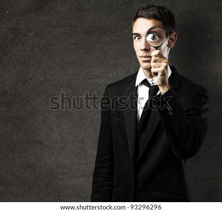 Portrait of a handsome young man looking through a magnifying glass against a grunge wall - stock photo