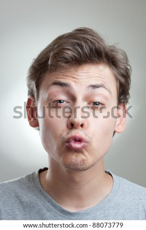 portrait of a handsome young man making a weired face, isolated on gray - stock photo