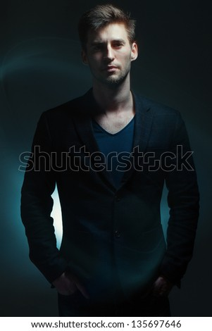 Portrait of a handsome young man on a dark background - stock photo