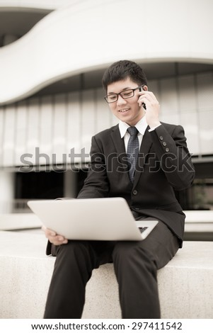 Portrait of a handsome young man on laptop outdoors