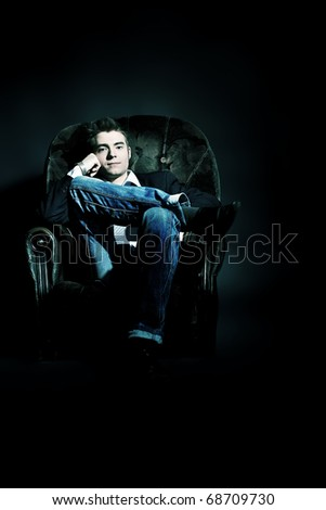 Portrait of a handsome young man posing over black background. - stock photo