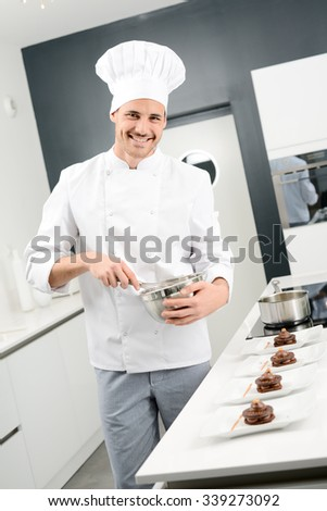 portrait of a handsome young man professional pastry cook preparing a chocolate dessert - stock photo