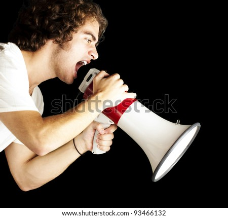 portrait of a handsome young man shouting with megaphone against a black background - stock photo