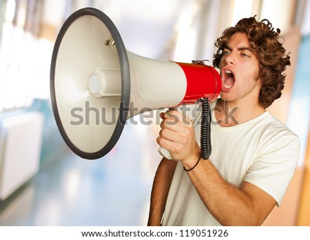 Portrait Of A Handsome Young Man Shouting With Megaphone, Indoor