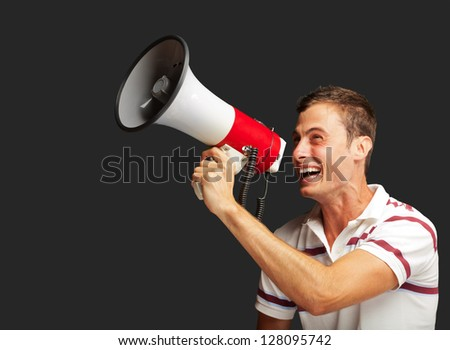 Portrait Of A Handsome Young Man Shouting With Megaphone On A Black Background