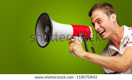 Portrait Of A Handsome Young Man Shouting With Megaphone On Green Background - stock photo