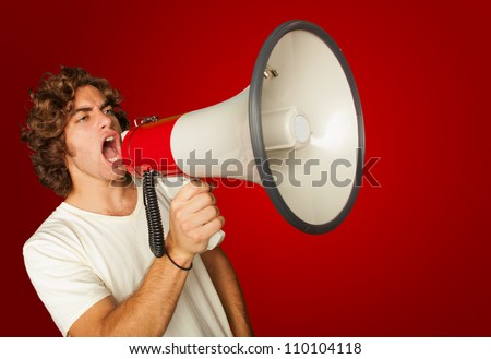 Portrait Of A Handsome Young Man Shouting With Megaphone On Red Background