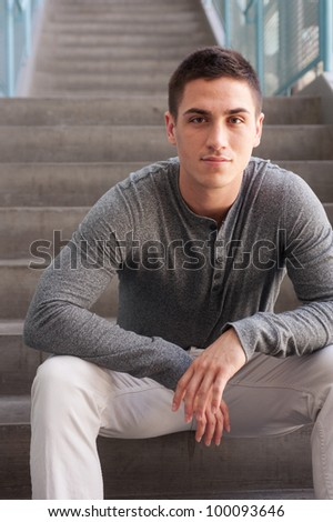 portrait of a handsome young man sitting on the steps inside a building - stock photo