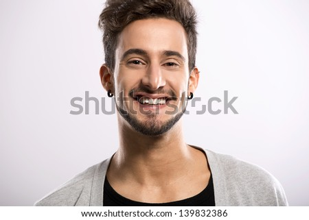 Portrait of a handsome young man smiling, over a gray background