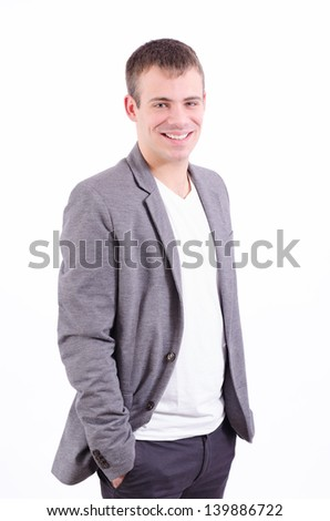 Portrait of a handsome young man smiling with hands in his pocket