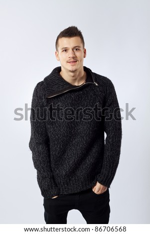 Portrait of a handsome young man standing with his hands in pocket against studio background - stock photo