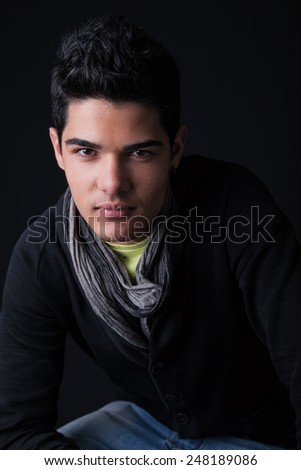 Portrait of a handsome young man. Studio shot on black background. - stock photo