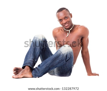 Portrait of a handsome young man wearing only jeans and sitting on a white background