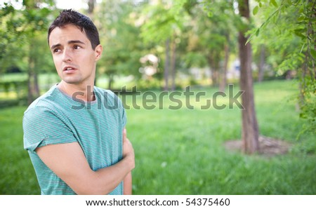 Portrait of a handsome young man while outdoors in a park on a lovely summer day - stock photo