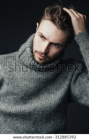 Portrait of a handsome young man with a beard in a warm sweater - stock photo