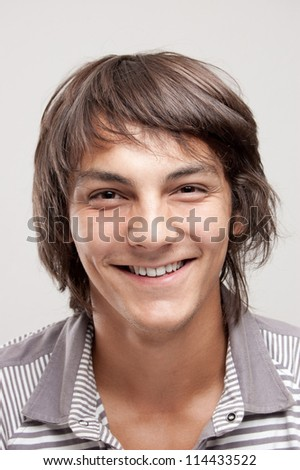 portrait of a handsome young man with long hair, isolated on gray - stock photo