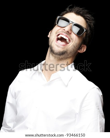 portrait of a handsome young man with sunglasses enjoying over black background