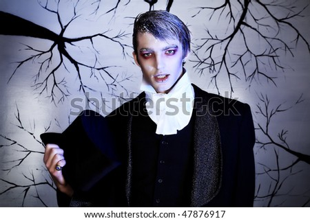 Portrait of a handsome young man with vampire style make-up. Shot in a studio. - stock photo