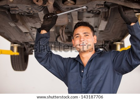 Portrait of a handsome young mechanic working on a suspended car at an auto shop and smiling - stock photo