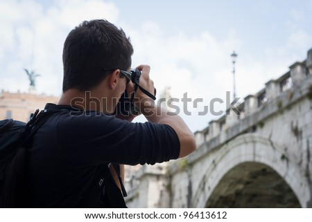 Portrait of a handsome young tourist taking photographs while sightseeing in Rome, Italy (with the Sant'Angelo bridge and castel in the background) - stock photo