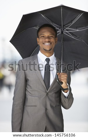 Portrait of a happy African American businessman holding umbrella - stock photo