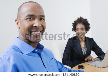 Portrait of a happy African American businessman with female coworker in the background