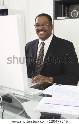 Portrait of a happy African American businessman working on computer at desk in office - stock photo