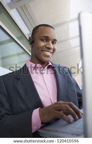 Portrait of a happy African American businessman working on laptop