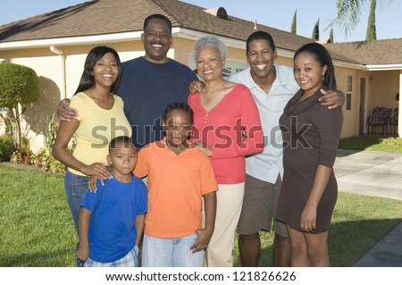 Portrait of a happy African American family standing together in front of the house - stock photo