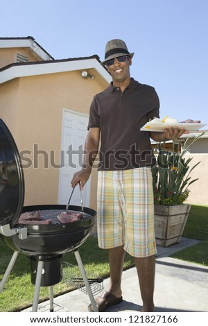 Portrait of a happy African American man cooking meat on barbecue - stock photo