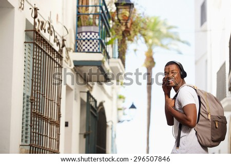 Portrait of a happy african american man traveling with bag and headphones - stock photo