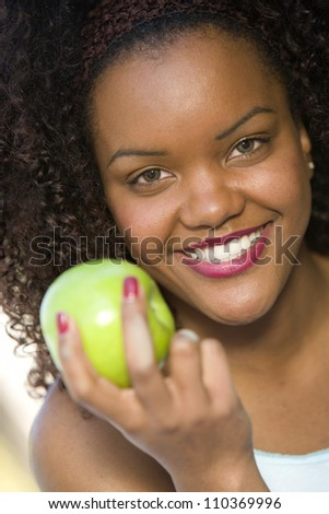 Portrait of a happy African American woman holding green apple